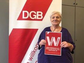 Christl Baudisch, ehemalige Vorsitzende des DGB-Frauenausschuss der DGB-Region Niederrhein mit Mottoplakat vom IFT
