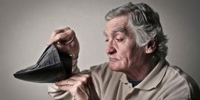 Älterer Mann schaut traurig in leere Geldbörse