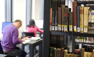 Bücherregal im Hintergrund zwei Menschen am Schreibtischen