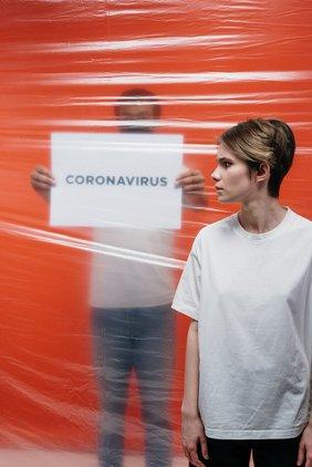 Frau mit Schild im Hintergrund -Coronavirus